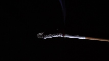 Cigarette in time-lapse isolated on black backround