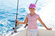 child girl sailing in fishing boat holding rod