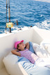 child girl sailing relaxed on boat deck ejoying a nap