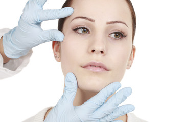 Arzt überprüft das Gesicht der Patientin vor dem Eingriff