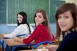 Beautiful three students sitting at school desks