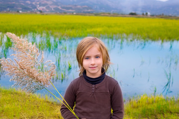 Blond kid girl outdoor holding spike in wetlands lake