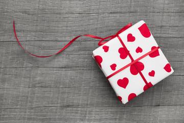 Ein Geschenk mit rot weißem Papier und Herzen zum Valentinstag