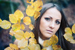 Close up portrait of young woman surrounded by autumn leaves.