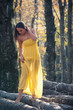 Beautiful young woman outdoors with yellow dress in the woods