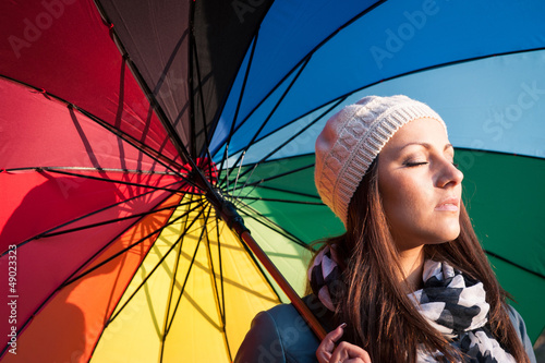 Young woman with multicolored umbrella.
