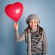 Young smiling girl with red heart balloon on blue background.