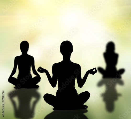 silhouettes of women practicing yoga lotus pose