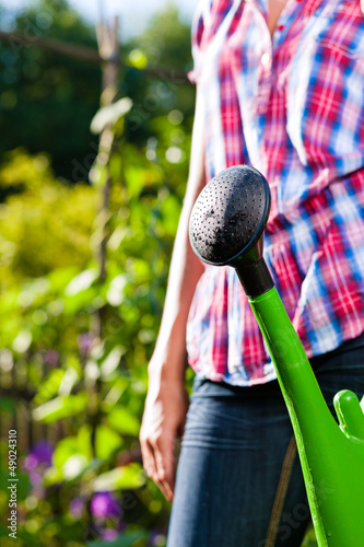 Woman in garden with watering can in hand