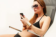 Frau im Bikini mit Handy