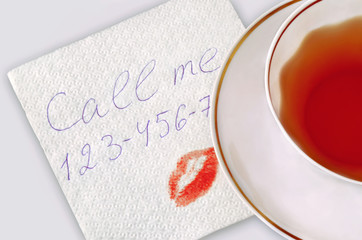 Napkin with phone number and kiss.