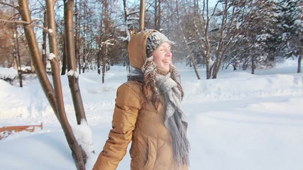 Girl in a park is happy about throwing snow