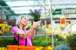 Young woman buying flowers at a garden center
