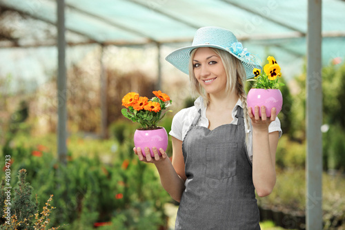 Female gardener holding flower pots in a garden