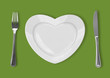 plate in shape of heart, table knife and fork on green backgroun
