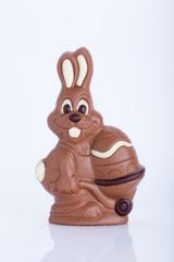 Osterhase aus Schokolade mit Osterei vor weißem Hintergrund