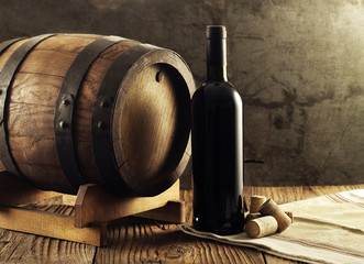 Red wine bottle and old barrel
