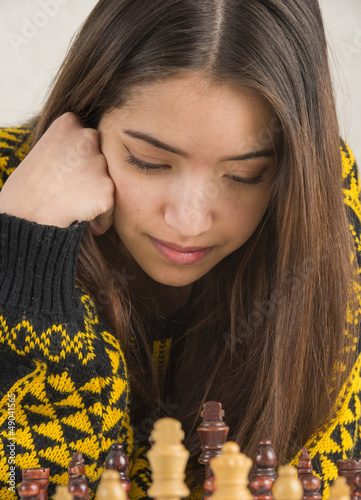Attractive young woman playing chess