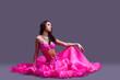 dancer in oriental pink costume sitting on floor