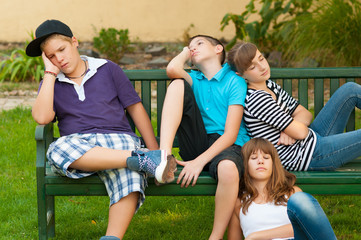 Teenage boys and girls resting on the bench