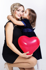 happy mother and her daughter with big red balloon