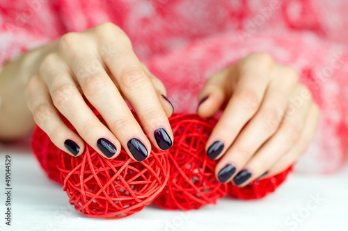 Hands with manicure touching decoration balls