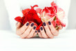 Hands with beautiful manicure holding bright flowers on white