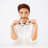 Beautiful businesswoman holding spectacles