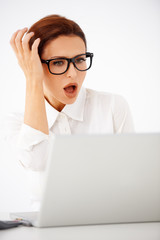 Shocked businesswoman looking at her laptop