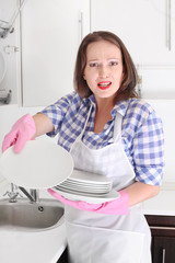 angry woman washing plate in kitchen