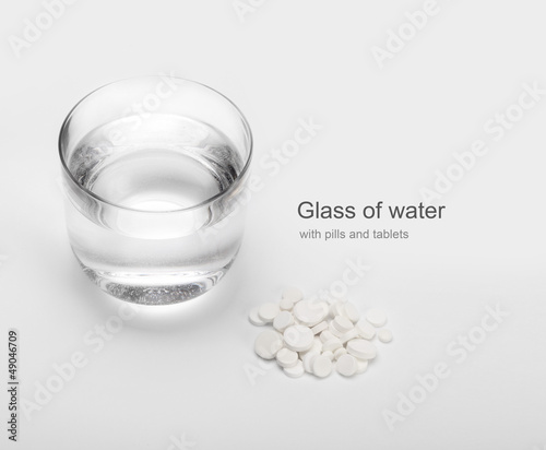 tablets and pills and glass of water