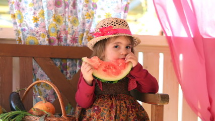 little girl sits on a verandah and eats  water-melon