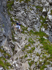 Man climbing a rock difficult and dangerous path using chains.