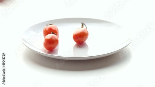 Woman puts tomatoes on a plate. Part 2