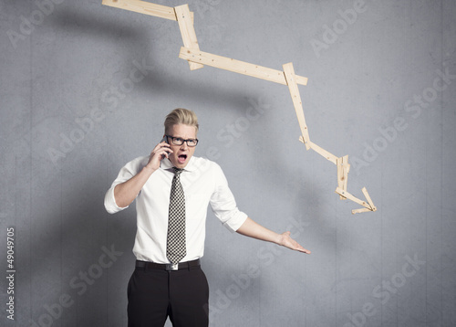 Angry businessman in front of graph pointing down.