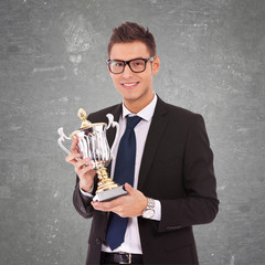 business man  with glasses holding a big trophy