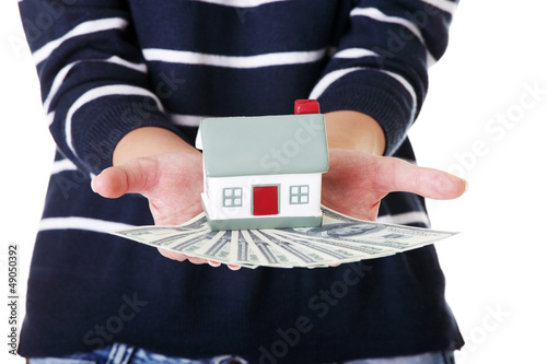Woman holding US dollars bills and house