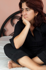 Hispanic woman sitting in her bed with a worried expression