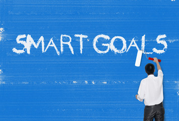 Man painting word on cement texture wall background, Smart Goals