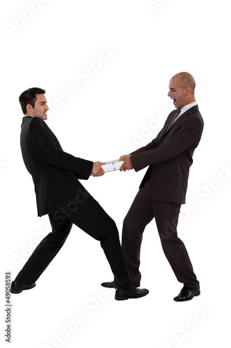Two businessman pulling in different directions