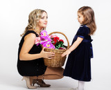 young mother with her little daughter with basket of flowers