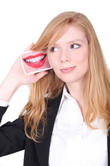 Young woman holding a photo of a mouth next to her ear