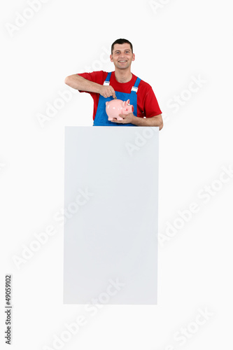 Worker with a piggy bank and a board for message