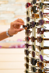 Young man at optician shopping sunglasses