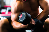 Man at Dumbbell training in gym - 49060742