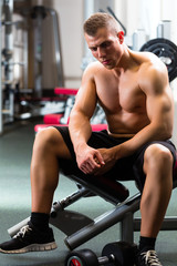 Man in gym or fitness studio on weight bench