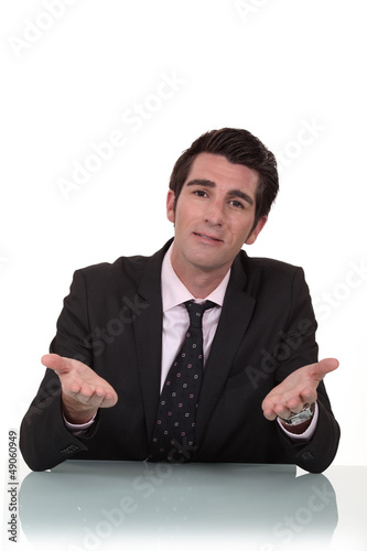 Businessman sitting at a desk talking to you