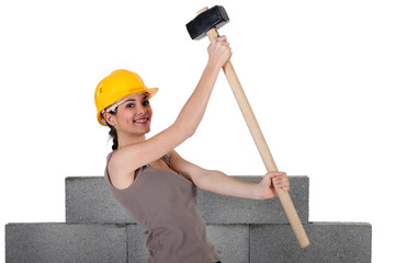 Woman lifting sledge-hammer in front of unfinished wall
