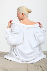 A female model taking her bathrobe off on her bed.