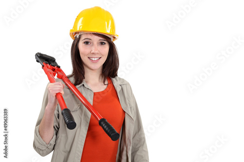 Young tradeswoman holding large clippers